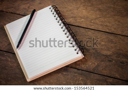 notebook and pen on wood table - stock photo