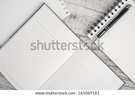 Notebook and pen on wood table for background