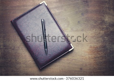 notebook and pen over a wooden background - stock photo