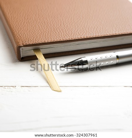 notebook and pen over white table