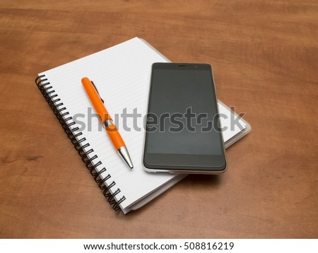 Notebook and pen with smartphone lying on the desk