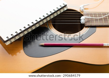 Notebook and pencil on guitar - stock photo