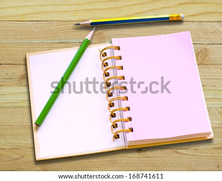 Notebook and pencil on vintage wood table for background and text