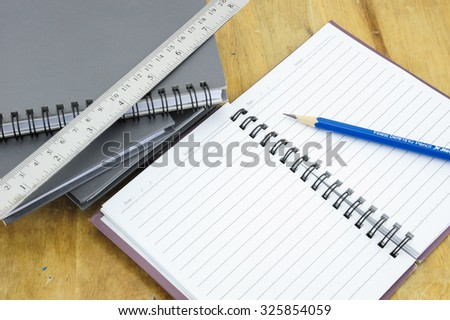 Notebook and pencil on weeden table and white background
