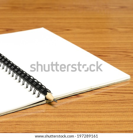 notebook and pencil on wood background - stock photo