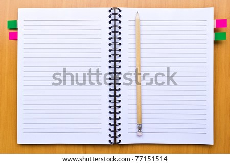 notebook and pencil on wood floor - stock photo