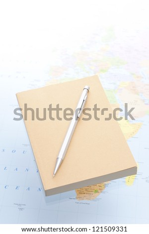 notebook and pencil on world map background