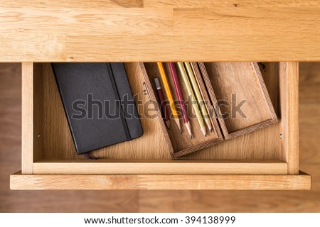Notebook and pencils in open desk drawer top view image. Drawing background - stock photo