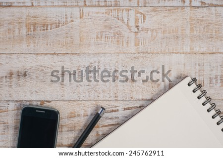Notebook and phone  on wood table for text and background - stock photo