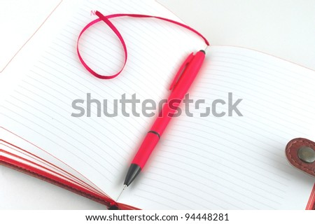 Notebook and red pen over white