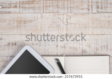 Notebook and tablet on wood table and background - stock photo