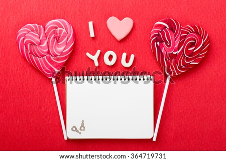 Notebook and two heart-shaped lollipops for Valentines day - stock photo