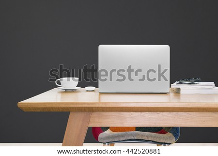 notebook computer and a cup of coffee on working table, notebook computer, mouse, coffee, books, glasses, modern chair, black wall background - stock photo
