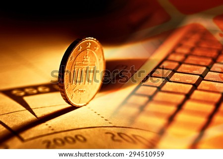 Notebook computer keyboard and euro coin. - stock photo