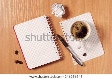 Notebook, crumpled paper, pen and coffee cup on desk, top view - stock photo