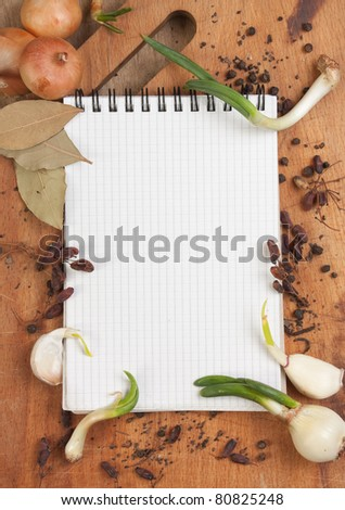 notebook for cooking recipes and spices on a wooden table