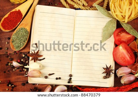 notebook for recipes and spices on wooden table - stock photo