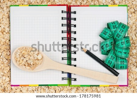 Notebook for the recipe of porridge on an oat background - stock photo
