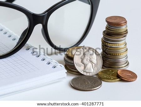 notebook, glasses and coins on a white background close-up, business, finance