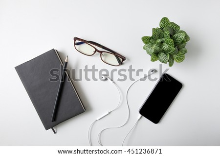 Notebook, glasses, smart phone, ear phone, pencil and plant potted on white desk background - stock photo