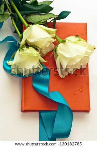 notebook in orange leather cover with white roses as a gift - stock photo
