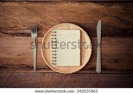 Notebook in the wooden plate with a spoon and a knife laying beside a table,Concept for perception