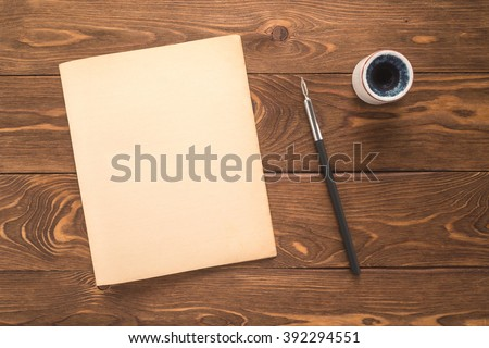 Notebook, ink pen, inkwell on a wooden background   - stock photo