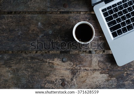Notebook (laptop) with hot coffee on old wood table. - stock photo