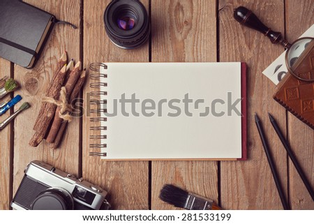 Notebook mock up for artwork or logo design presentation with film camera and lens. View from above - stock photo