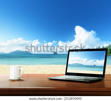 notebook on table and tropical beach - stock photo