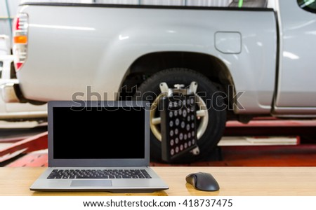 Notebook on the table, blur image of inside tire shop as background.