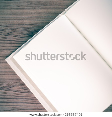notebook on wood background vintage style - stock photo