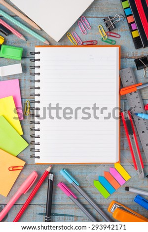 Notebook paper and school or office tools on blue vintage wood table for background - stock photo