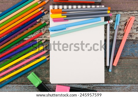 Notebook paper and school or office tools on vintage wood table  for background - stock photo