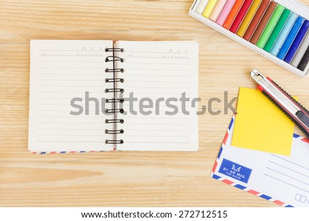 Notebook paper and school or office tools on wood table for background