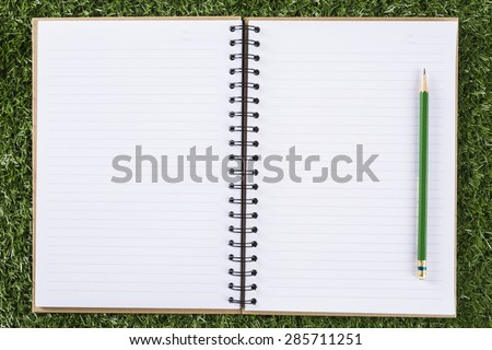 notebook paper background with pencil on green grass background