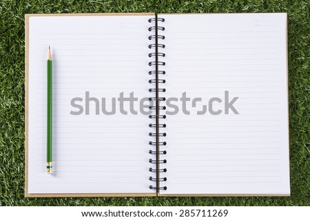 notebook paper background with pencil on green grass background  - stock photo