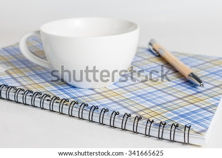 Notebook pen and cup of coffee isolated on a white background - stock photo