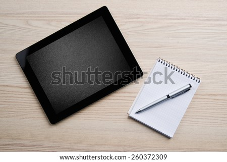 Notebook, pen and digital tablet pc with blank dark screen on wood table background. Business concept - stock photo