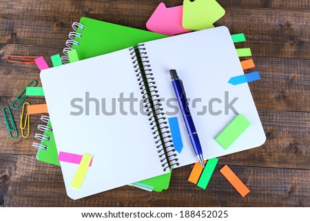 Notebook, pen, and stickers on wooden background - stock photo