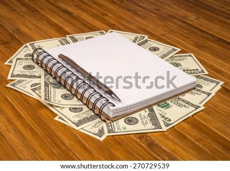 notebook pen Dolar money on a wooden table - stock photo