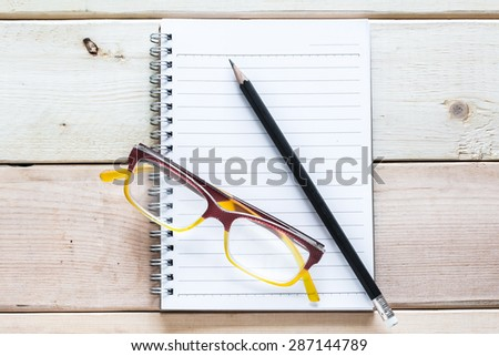 notebook , pencil and eyeglasses  on wood table - stock photo