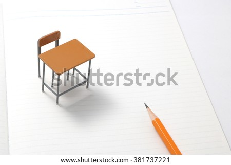 Notebook, pencil and miniature desk  / Study or student insurance image - stock photo