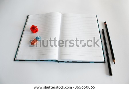 Notebook, two pencils, eraser and sharpener - stock photo