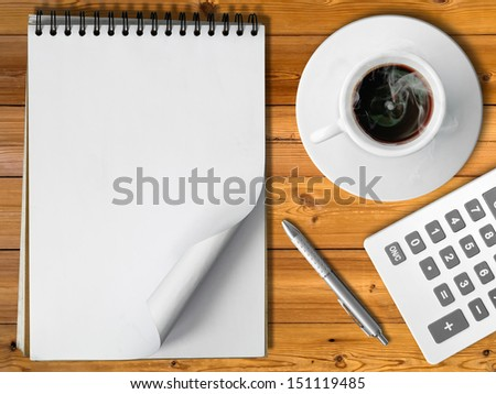 Notebook White cup of hot coffee silver pen and Silver pen on Wood table - stock photo