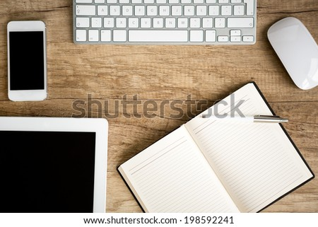 Notebook wit tablet on wooden table, top view - stock photo