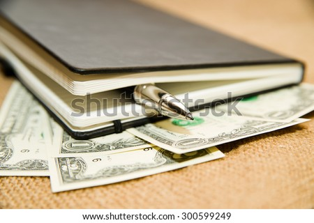 notebook with a blank sheet, pen and money on the old tissue - stock photo