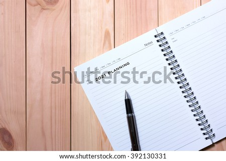 Notebook with Black Pen. Writting 2021 Planning with wooden pallet background.