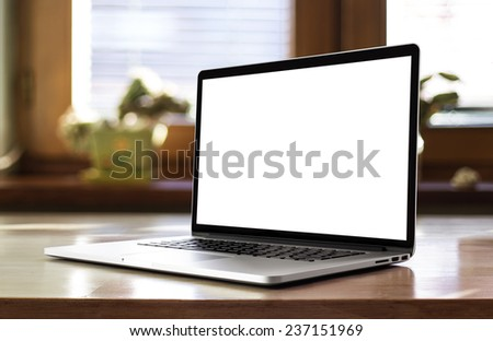 Notebook with blank screen on table in living room. - stock photo