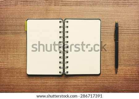 Notebook with Blank sheet of paper and Pen on wooden table background. Writing Idea concept - stock photo